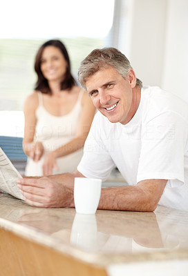 Buy stock photo Happy mature man atkitchen counter reading newspaper and coffee with his wife in background