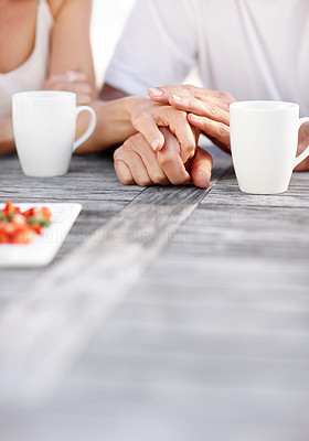 Buy stock photo Cropped image of couple holding hands at the breakfast table
