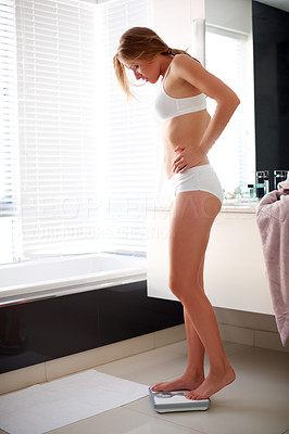 Buy stock photo Portrait of a sexy young girl measuring her weight while standing on weighing machine