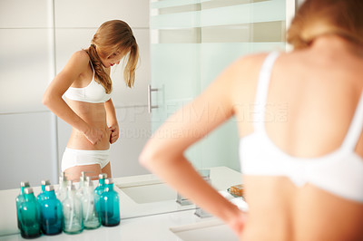 Buy stock photo Portrait of a hot young female checking fats on her tummy in the bathroom mirror