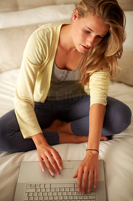 Buy stock photo Portrait of a beautiful young female working on laptop while sitting on the  bed at home