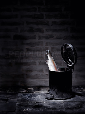 Buy stock photo Picture of a rubbish bin with a salmon in it. Dark, gloomy lighting. Wasting natures resources.
