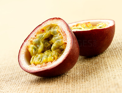 Buy stock photo Shot of a passionfruit, cut open. On a rough table cloth