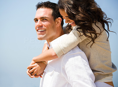 Buy stock photo Side view of a smiling young couple piggybacking. Man and woman in love.