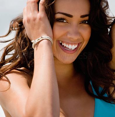 Buy stock photo Close up of a beautiful young lady smiling, with her hand in her hair.