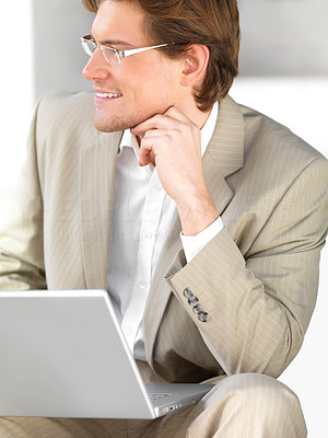 Buy stock photo Young businessman looking away while using laptop in an urban setting
