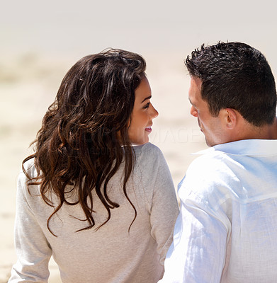Buy stock photo Young couple sitting together and looking at each other