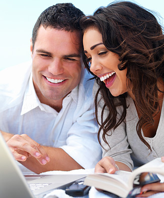 Buy stock photo Close up of a happy young couple looking at laptop