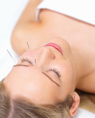 Buy stock photo Portrait of a beautiful woman lying peacefully with acupuncture needles in her brow and cheek - copyspace