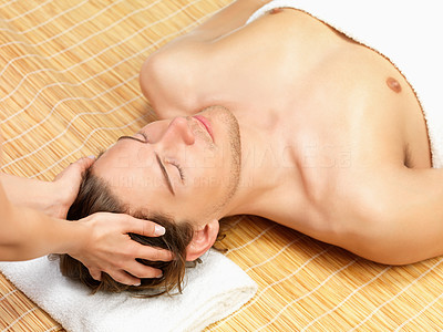 Buy stock photo Shirtless man lying on mat and receiving massage by two female hands.