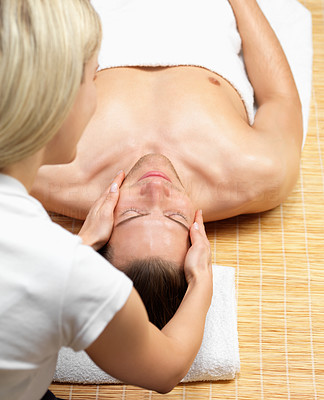 Buy stock photo Young man relaxing on holiday while blond woman giving spa treatment