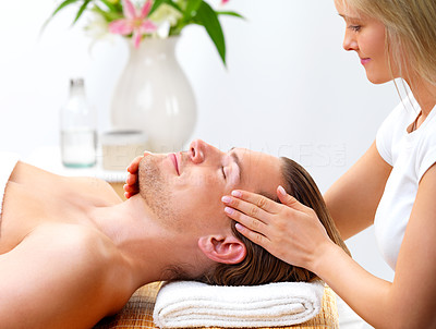 Buy stock photo Young man with eyes closed receiving facial massage from a beautiful lady
