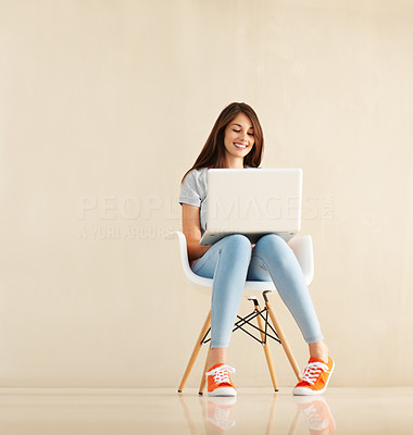 Buy stock photo Full length of a smiling young woman sitting on a chair using her laptop next to large copyspace