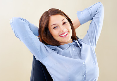Buy stock photo Portrait of pretty businesswoman sitting on chair with hands behind head and smiling