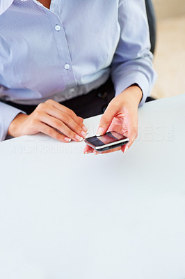 Buy stock photo Cropped view of businesswoman sitting at table holding mobile phone