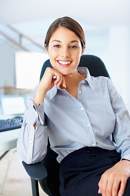 Buy stock photo Portrait of pretty young businesswoman sitting on an office chair and smiling