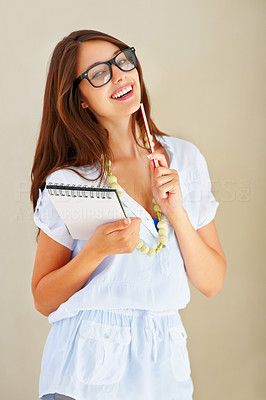Buy stock photo Portrait of beautiful young woman holding notepad and pen