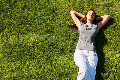 Buy stock photo Top view of cute young woman lying in the grass and relaxing with hands behind head