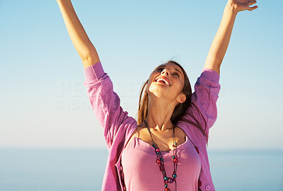 Buy stock photo Beautiful young woman standing against sky with hands raised