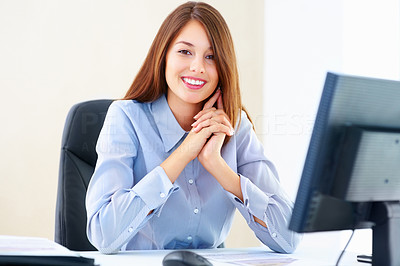 Buy stock photo Portrait of pretty female executive sitting at an office table and smiling
