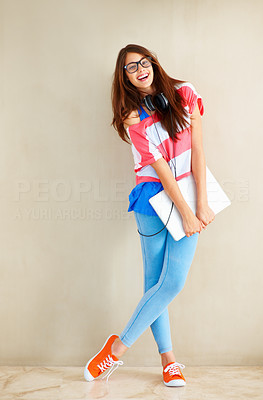 Buy stock photo Full length of beautiful young girl in retro glasses standing near wall and holding laptop next ot copyspace