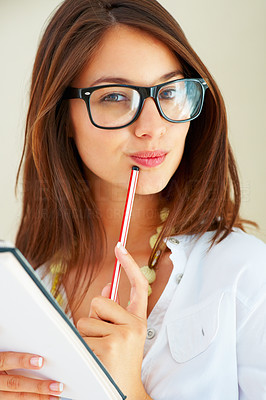 Buy stock photo Closeup of young woman in retro glasses with notebook and pen planning her daily schedule