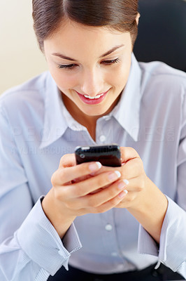 Buy stock photo Closeup of cute young female executive reading text message on her mobile phone and smiling