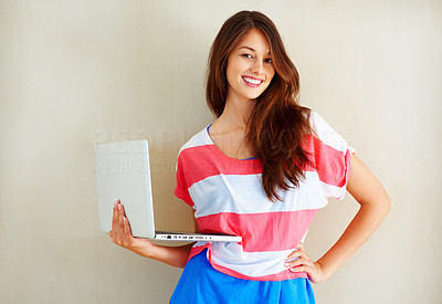 Buy stock photo Portrait of pretty woman smiling at you while holding a laptop against a wall - copyspace