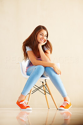 Buy stock photo Full length of young woman sitting casually on chair and giving you beautiful smile