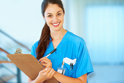 Buy stock photo Portrait of attractive female doctor writing on medical chart - copyspace