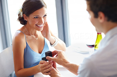 Buy stock photo Young man romantically proposing to girlfriend and offering engagement ring