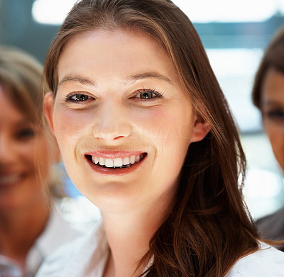Buy stock photo Closeup of young female executive smiling with team behind her