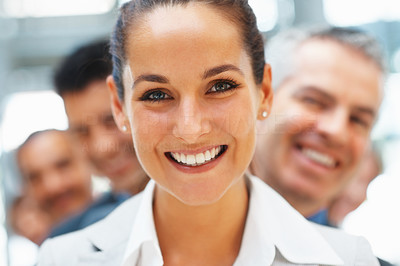 Buy stock photo Focus on smiling businesswoman with happy colleagues behind her