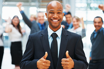 Buy stock photo Businessman giving two thumbs up with colleagues throwing hands in air in background