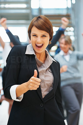 Buy stock photo Businesswoman holding thumbs up with enthusiastic team in background
