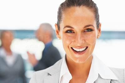 Buy stock photo Closeup of pretty female executive with colleagues in background