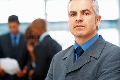 Buy stock photo Closeup of handsome executive with colleagues in background
