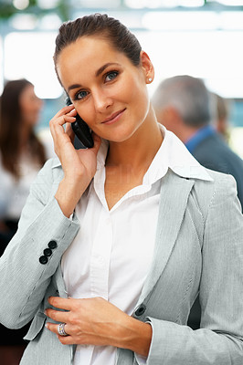 Buy stock photo Pretty business woman using cell phone with colleagues in background