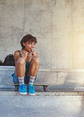 Buy stock photo Shot of a young woman sitting on her skateboard