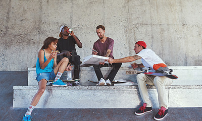 Buy stock photo Shot of a group of skaters having lunch together