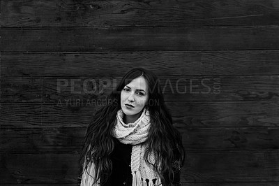 Buy stock photo Black and white shot of a young woman posing against a wooden background