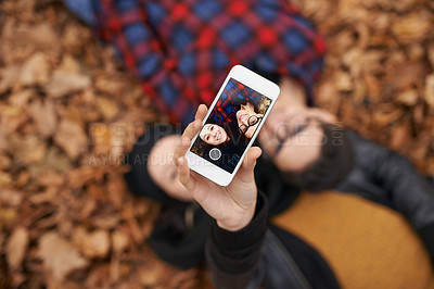 Buy stock photo Shot of a young couple taking a selfie on an autumn day in the park