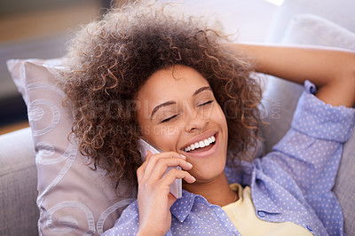 Buy stock photo Shot of a young woman talking on her cellphone while lying on her living room sofa
