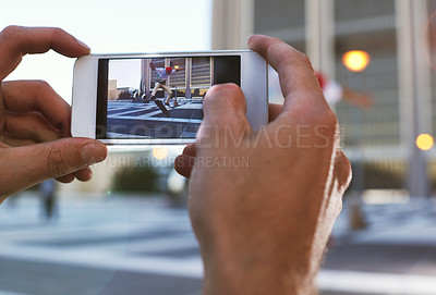 Buy stock photo Cropped shot of a man taking a picture of his friend doing tricks on his skateboard