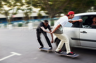 Buy stock photo Shot of two skaters holding on to a moving car