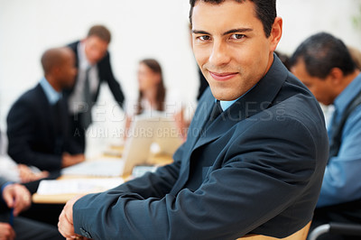 Buy stock photo Handsome executive looking at you during a company meeting