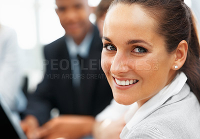 Buy stock photo Closeup of pretty executive with colleagues in distance