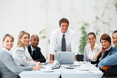 Buy stock photo Executive in charge, standing at head of table with team around table