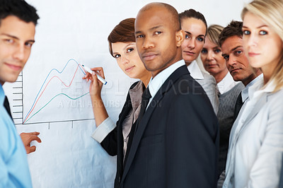 Buy stock photo A business team having a meeting around a graph on a whiteboard