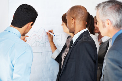 Buy stock photo Female executive drawing an illustrative profit graph on a white board while surrounded by colleagues